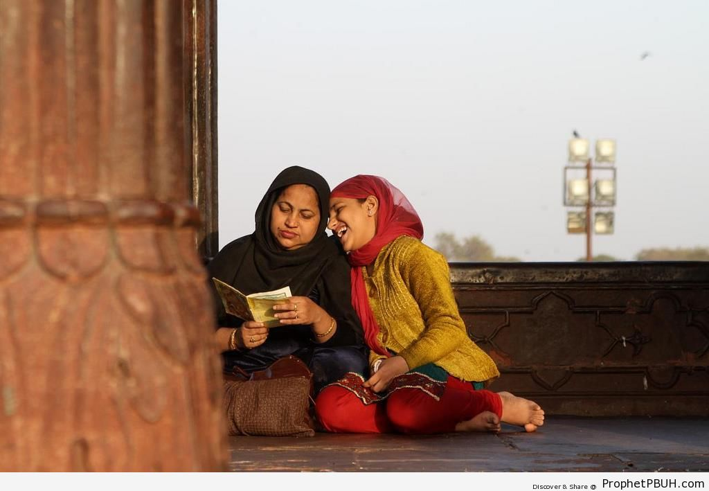 Laughing Daughter and Praying Mother at Jama Masjid in Old Delhi, India - Delhi, India -Picture