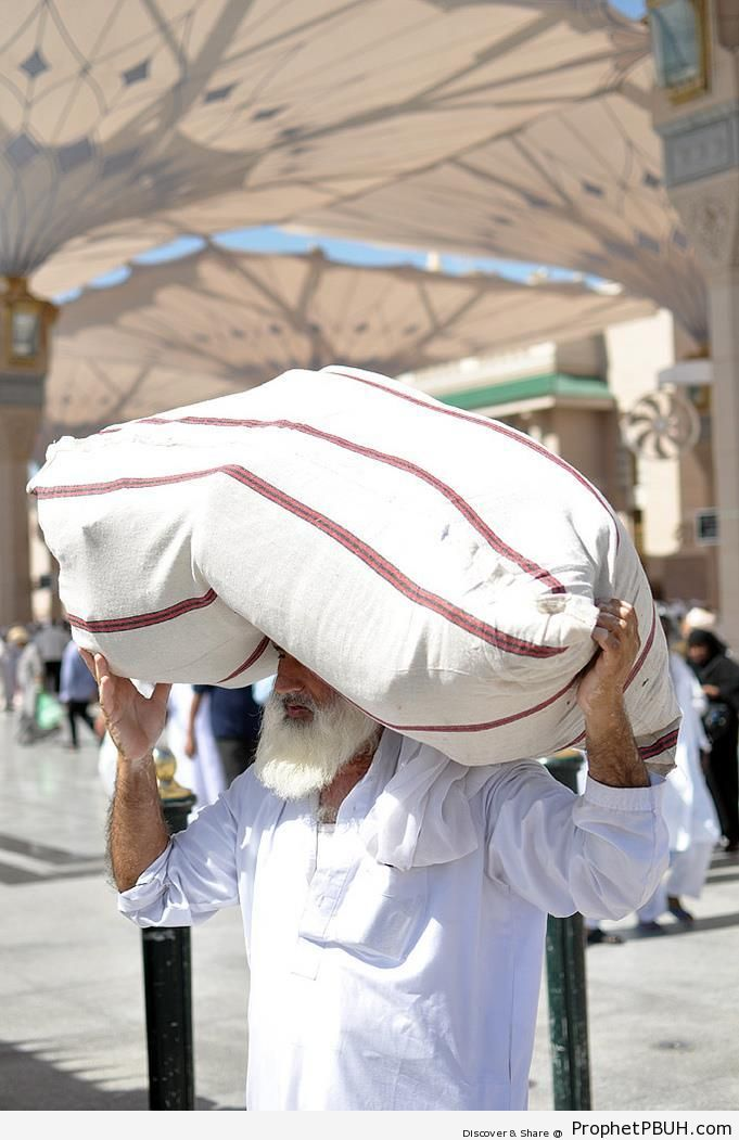 Man Carrying Load Under Masjid an-Nabawi Umbrellas - Al-Masjid an-Nabawi (The Prophets Mosque) in Madinah, Saudi Arabia -Picture