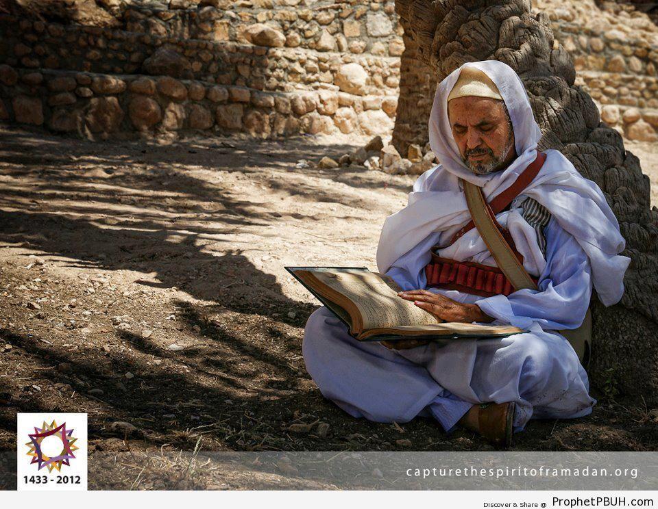 Man Reading Quran Under Tree - Photos